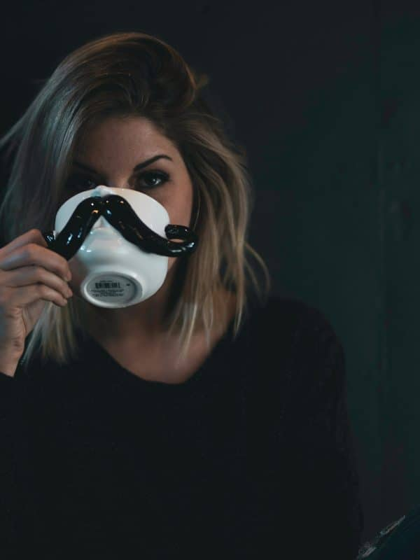 woman drinking from a mustasch cup